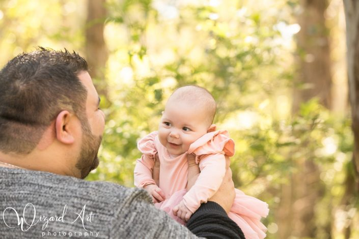 Baby girl in pink looking lovingly at her father