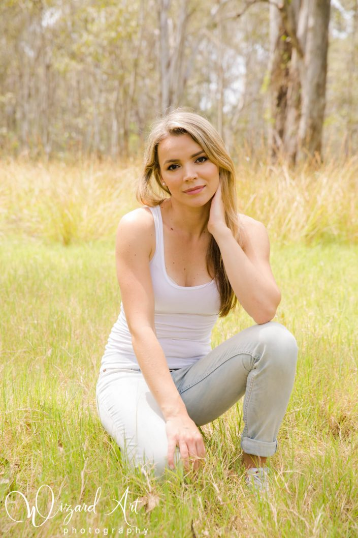 Beautiful woman in jeans and a white tank kneeling in long grass at nurragingy Reserve, Doonside.