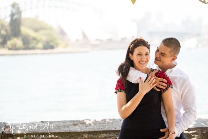 Couple cuddling at Sydney Botanic Gardens with a view of Sydney Opera House.