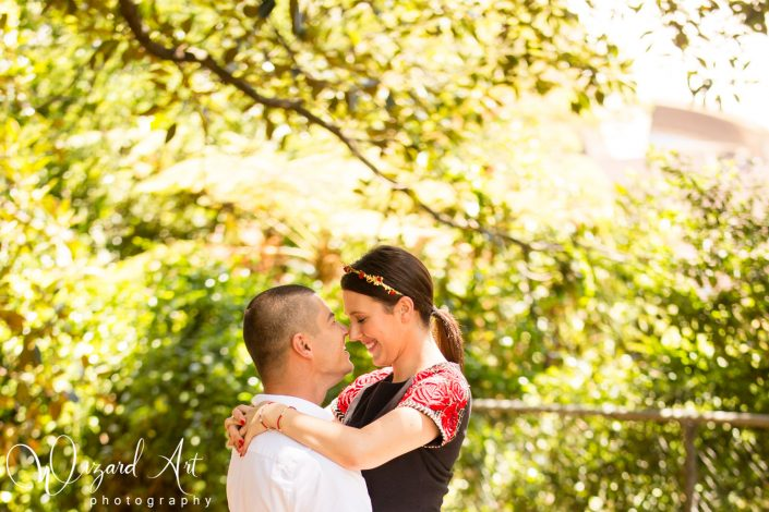 Man lifting woman and embracing nose to nose at Sydney Botanic Gardens.