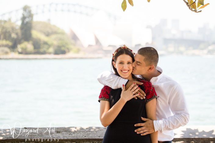 Man kisses fiance's cheek and embraces her at Sydney Botanic Gardens with a backdrop of Sydney Opera House.