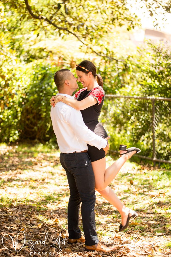 Man lifting his fiance in the air and embracing nose to nose at Sydney Botanic Gardens.