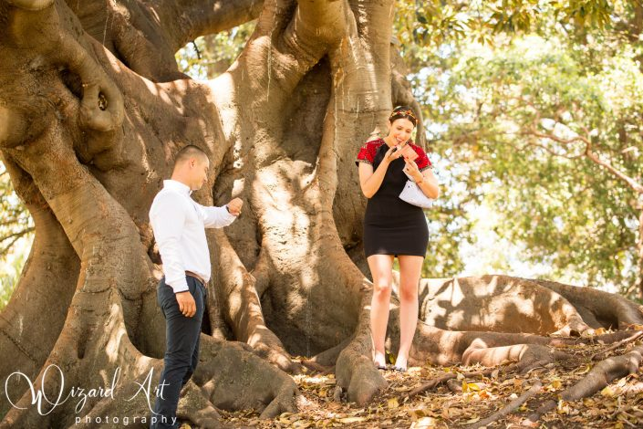 Man waiting for his fiance to apply lipstick during photo shoot. Welcome to married life.