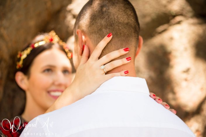 Woman tenderly holds fiance's head while showing stunning tear drop diamond halo engagement ring.