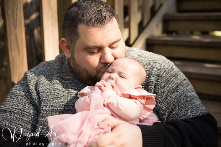 Father lovingly kissing baby daughter