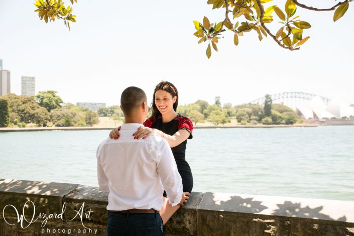 Girl sitting on wall holding partner's shoulders and staring into his eyes at Sydney Botanic Gardens with a backdrop of the Sydney Harbour bridge.