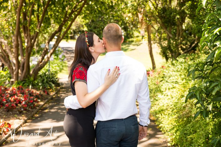 Girl lovingly kisses her fiance's cheek at Sydney Botanic Gardens.