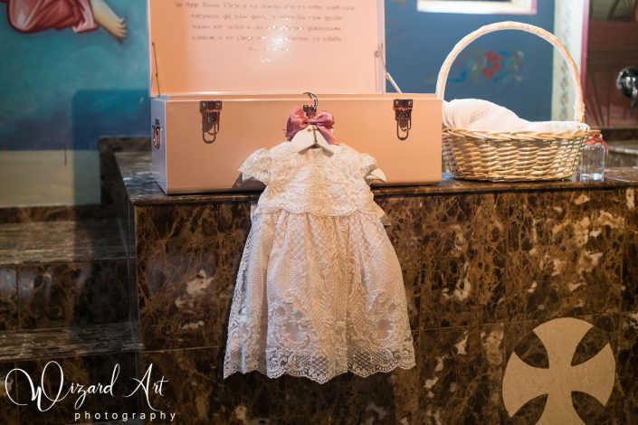 Baby girl christening gown hanging on custom christening box.