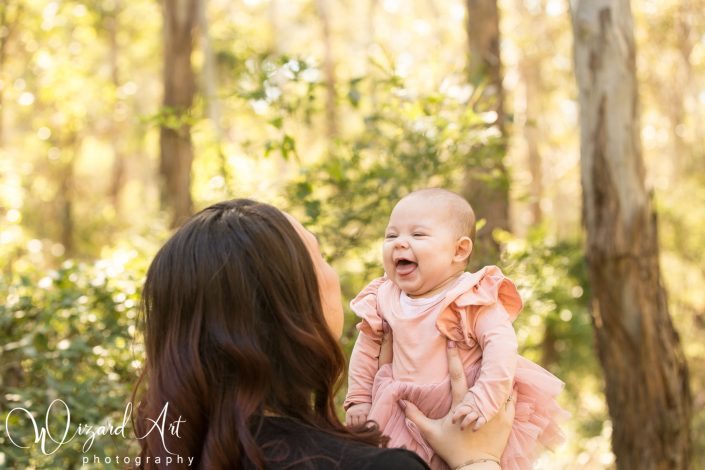 Happy baby girl in pink laughing with mummy