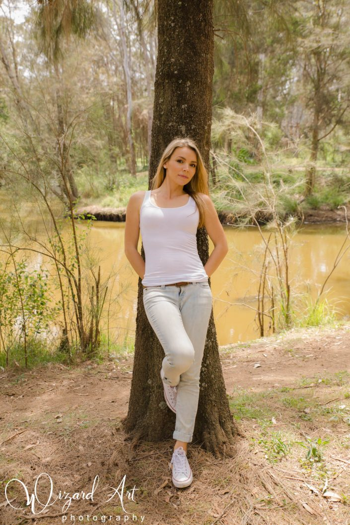 Woman leaning against a tree in jeans and a tank at Nurragingy Reserve, Doonside.