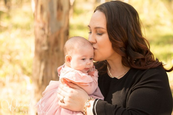 Mum kissing baby girl during outdoor family photography session