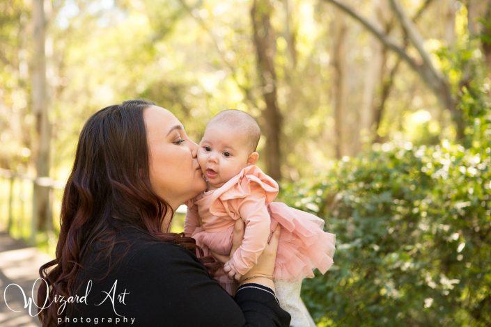Mummy kissing baby girl