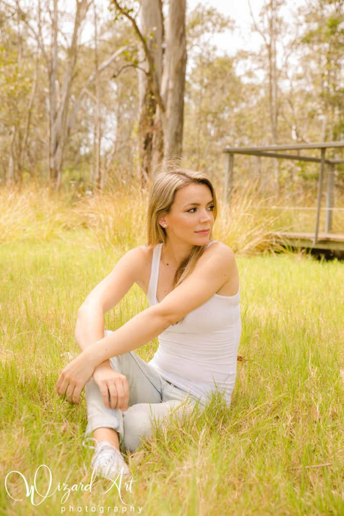 Woman wearing jeans and tank sitting in long grass at Nurragingy Reserve, Doonside.
